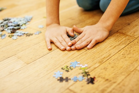 loving hands: little kid playing with puzzles on wooden floor together with parent, lifestyle people concept, loving hands to each other, warm wooden interior Stock Photo