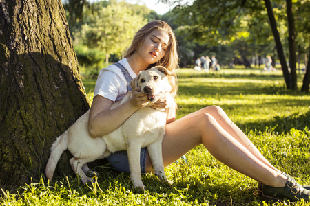 poquito: young attractive blond woman playing with her dog in green park at summer, lifestyle people concept, true friendship