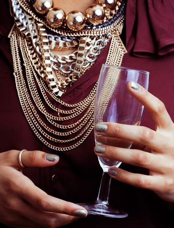 gold facial: young african-american woman drinking champagne, holding glass, wearing lot of golden jewelry, body part Stock Photo