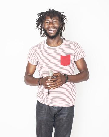 muchacho joven afroamericano hermoso canto emocional con el micrófono aislado en el fondo blanco, en movimiento haciendo un gesto sonriente, las personas concepto de estilo de vida