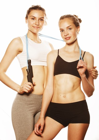 inflated: two sport girls measuring themselves isolated on white, inflated press