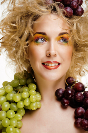 beautiful young woman portrait excited smile with fantasy art hair makeup style, fashion girl with creative food fruit orange, grapes, citrus make up, happy looking at camera cheerful Foto de archivo