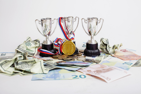 real trophy: Sport winning concept: three cups among diverse currencies euro, dollar, rubl, gold medal first place close up