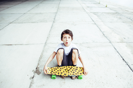 funy: little cute boy with skateboard on playground alone training, making funy faces close up