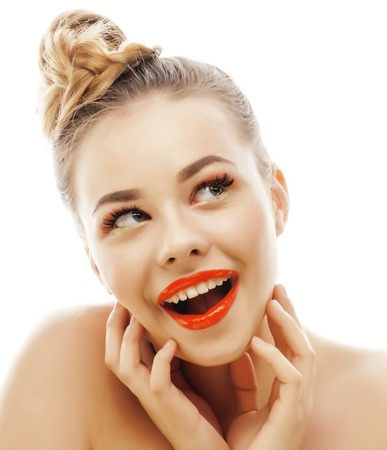young blond woman with bright make up smiling pointing gesturing emotional isolated like doll lashes on white, real people concept