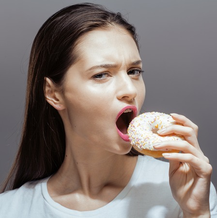 habbit: young pretty real thin girl with donut close up, unhealthy habbit bulimia concept Stock Photo
