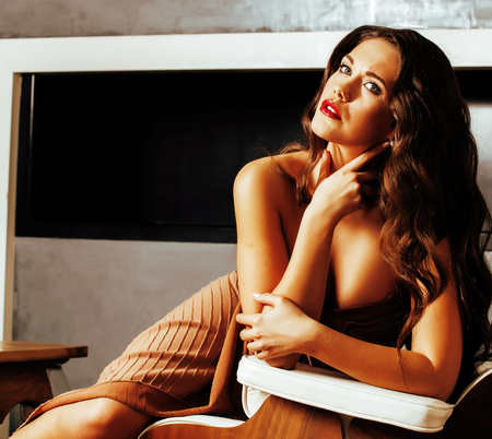 solitariness: beauty yong brunette woman sitting near fireplace at home, winter warm evening in interior, waiting to celebrate womans day
