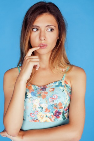 young pretty adorable woman close up like doll posing, natural makeup emotional gesturing on blue background Stock Photo