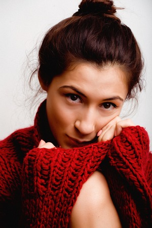 young pretty woman in sweater and scarf all over her face, winter cold close up, lifestyle people concept Stock Photo