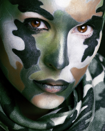 face paint: Beautiful young fashion woman with military style clothing and face paint make-up, khaki colors, halloween celebration close up, green pattern