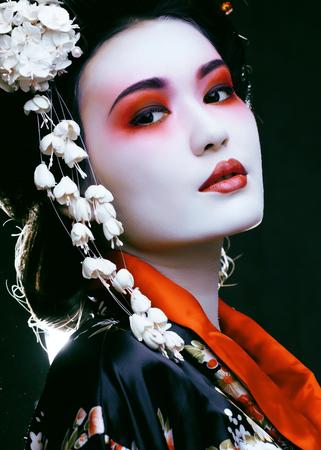 Young beautiful asian womans portrait, geisha in kimono on black