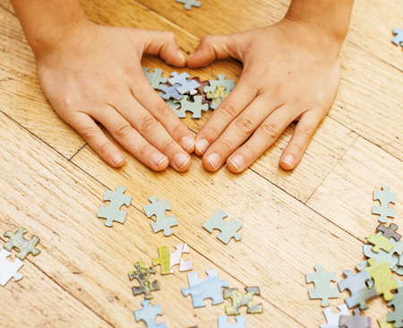 loving hands: little kid playing with puzzles on wooden floor together with parent, lifestyle people concept, loving hands to each other, warm wooden interior close up