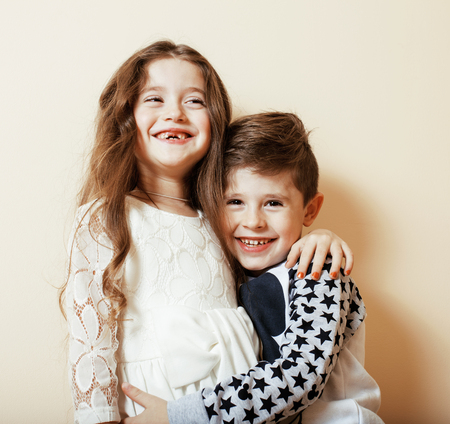 little cute boy and girl hugging playing on white background, happy family smiling close up Stock Photo