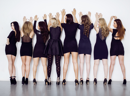 squad: Many diverse women in line, wearing fancy little black dresses, party makeup, vice squad concept, lifestyle people