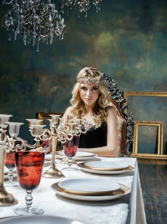 heir: young blond woman wearing crown in fairy luxury interior with empty antique frames total wealth Stock Photo