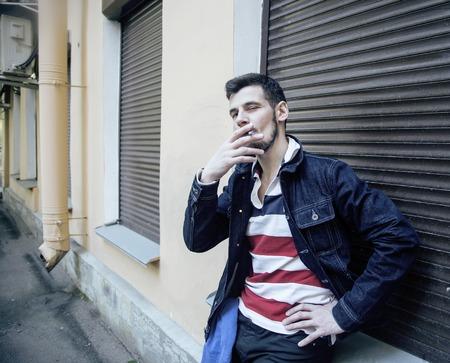 tough guy: middle age man smoking cigarette on backjard, stylish tough guy, lifestyle people concept