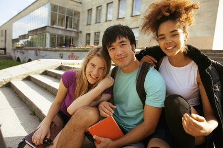 multy: cute group of teenages at the building of university with books huggings, smiling, back to school