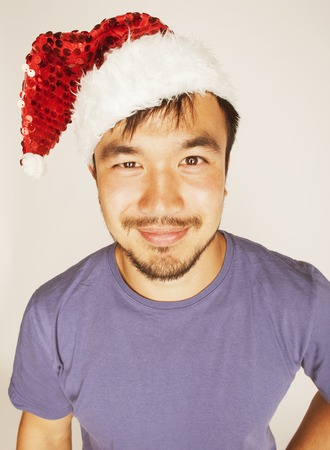 funy: funy exotical asian Santa claus in new years red hat smiling on white background Stock Photo