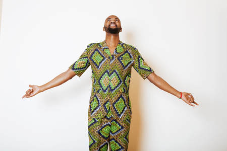 country nigeria: portrait of young handsome african man wearing bright green national costume smiling gesturing, entertainment stuff Stock Photo