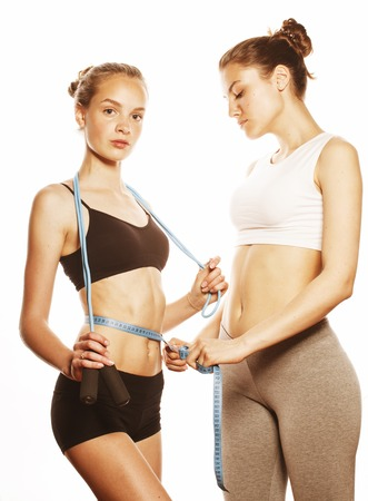 taping: two sport girls measuring themselves isolated on white, inflated press