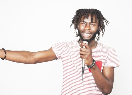 young handsome african american boy singing emotional with microphone isolated on white background, in motion gesturing smiling, lifestyle people concept Stok Fotoğraf