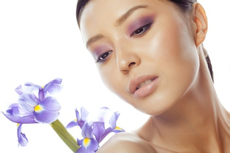 spa flower: young pretty real asian woman with flower purple orchid close up isolated on white background spa, healthcare concept