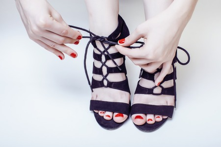 hight: fashion concept people: woman with red nails manicure pedicure tying shoelaces on hight heel shoes isolated on white background, mani pedi together Stock Photo