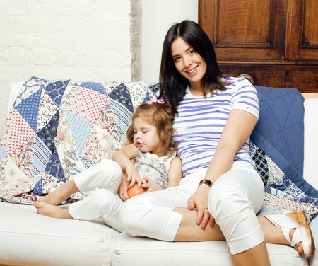 warm things: Portrait of smiling young mother and daughter at home, happy family together having fun, lifestyle people concept close up