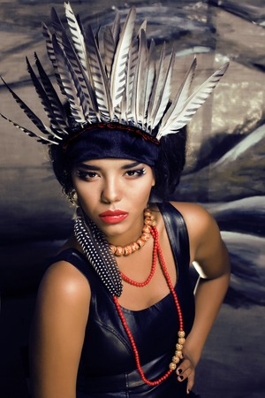 hallowen: young pretty woman with make up like red indian, futher in hair, fashion hallowen concept creative