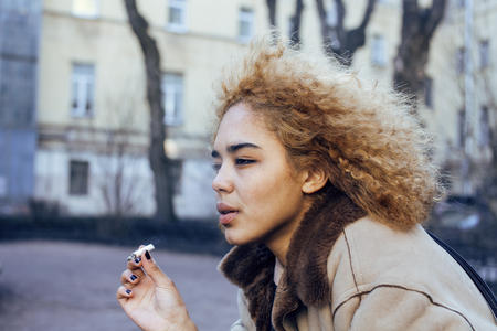 junky: young pretty girl teenage outside smoking cigarette close up, looking like real junky, social issues concept Stock Photo