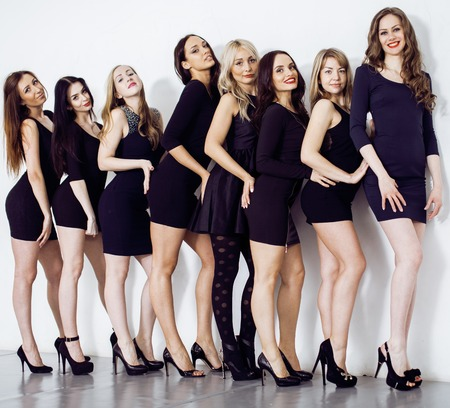 squad: Many diverse women in line, wearing fancy little black dresses, party makeup, vice squad concept lifestyle Stock Photo