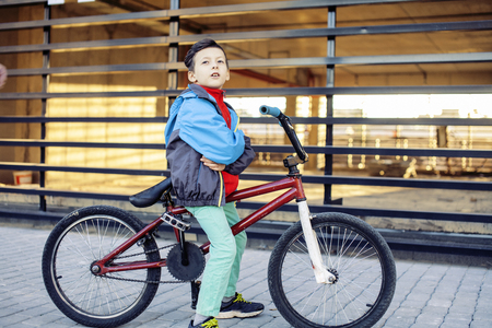 young kid on cool bmx bicycle riding outside, lifestyle people concept close up