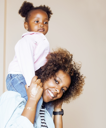 adorable sweet young afro-american mother with cute little daughter, hanging at home, having fun playing smiling, lifestyle people concept close up