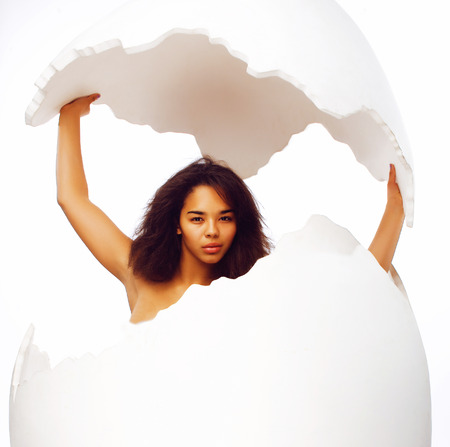 black skined african american young woman in big crashed egg Foto de archivo