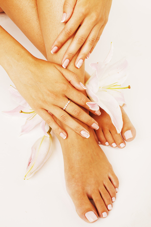 mani: manicure pedicure with flower lily close up isolated on white perfect shape hands feet, mani pedi close up Stock Photo