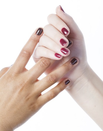 manicured hands: two different nathion manicured hands on white isolated, african with caucasian close up, gesturing, making shape spa salon