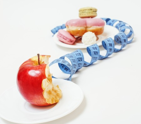 new diet concept, question sign in shape of measurment tape between red apple and donut isolated on white close up