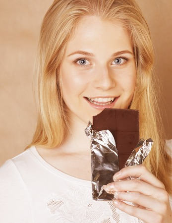 habbit: young cute blond girl eating chocolate and drinking coffee close up on warm background