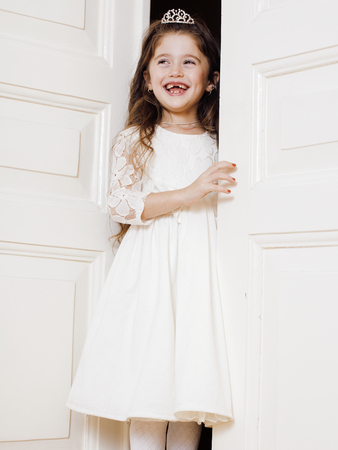 welldressed: little cute girl at home, opening door well-dressed in white dress, adorable milk fairy teeth, curious child