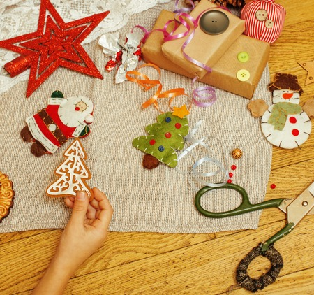 handmade christmas gifts in mess with toys, candles, fir, ribbon, tree cone wooden vintage, post card view, kids hand