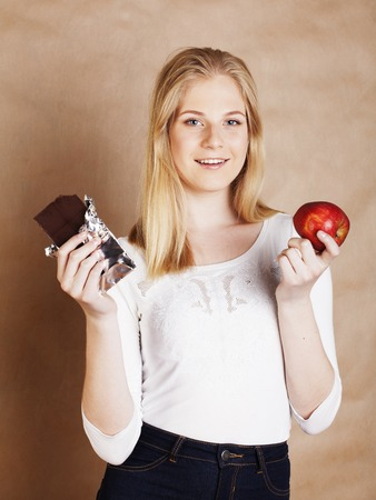 habbit: young beauty blond teenage girl eating chocolate smiling, choice between sweet and red apple Stock Photo