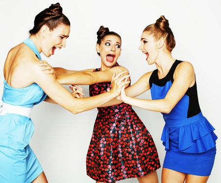 three elegant fashion woman fighting on white background, bright dresses evil faces, lifestyle people concept