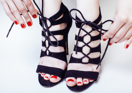 hight: fashion concept people: woman with red nails manicure pedicure tying shoelaces on hight heel shoes isolated on white background close up Stock Photo