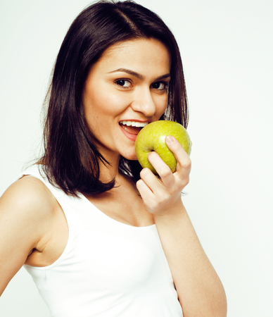 young pretty brunette girl with green apple in studio isolated on white background, healthcare good food concept, lifestyle people close up