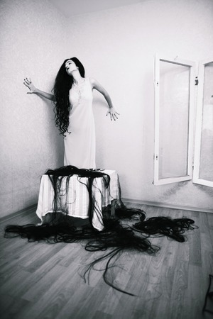 fearing: beauty girl cuting her hair in empty fearing room with cutted hair, halloween creepy celebration art, scary postcard view black and white