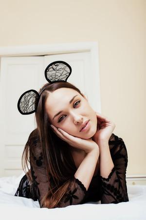 lapin sexy: jolie jeune femme brune portant des oreilles sexy en dentelle de souris, portant attente rêver dans son lit fermer