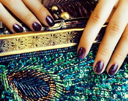 dita della donna di bellezza con la borsa di lusso della tenuta del manicure