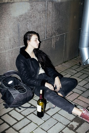 junky: young poor ttenage girl sitting at dirty wall on floor with bottle of vine, poor refugee alcoholic, hopeless homeless woman in depression, real junky concept close up