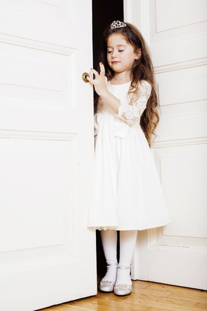 welldressed: little cute girl at home, opening door well-dressed in white dress and tiara, adorable milk fairy teeth