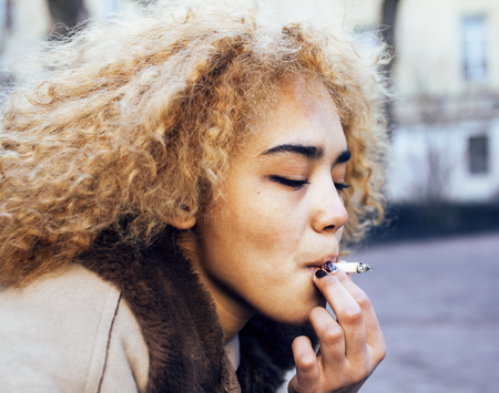 junky: young pretty girl teenage outside smoking cigarette, looking like real junky, social issues concept close up Stock Photo